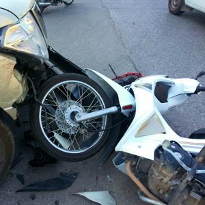 車と正面衝突して横に倒れている原付バイクの写真