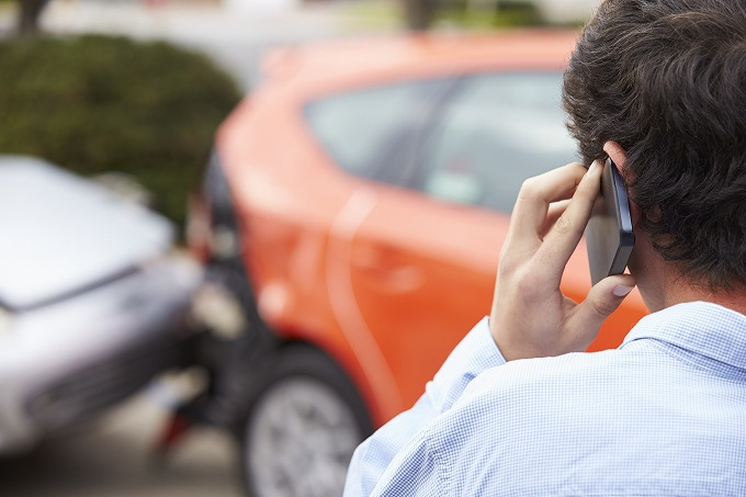 交通事故の状況を見ながら電話をする加害者のイメージ画像