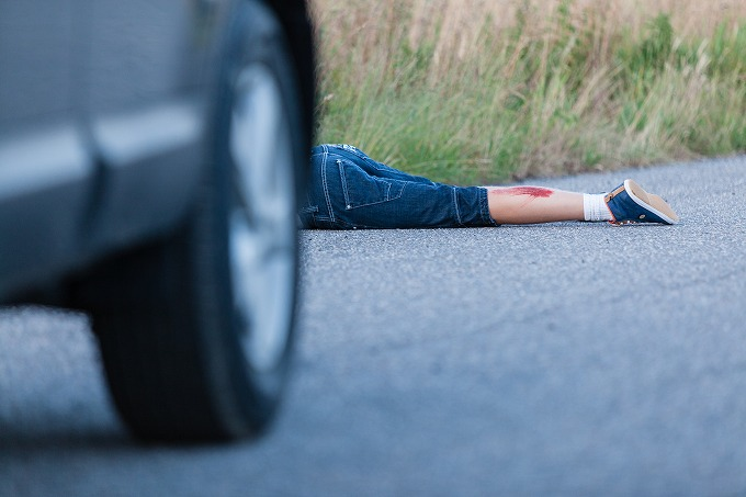 車にひかれて倒れている被害者と車のイメージ写真