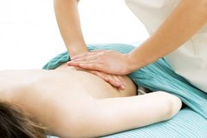 背中を手で按摩する柔道整復師の写真