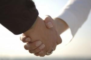 示談交渉で和解して握手をする被害者と加害者のイメージ画像