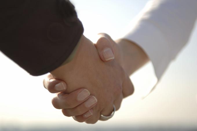 交通事故の加害者と被害者が和解をして握手をしているイメージ画像