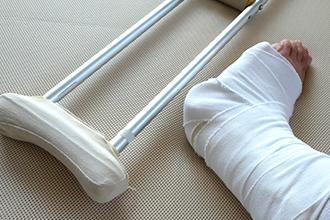 交通事故で骨折した足と松葉杖の画像