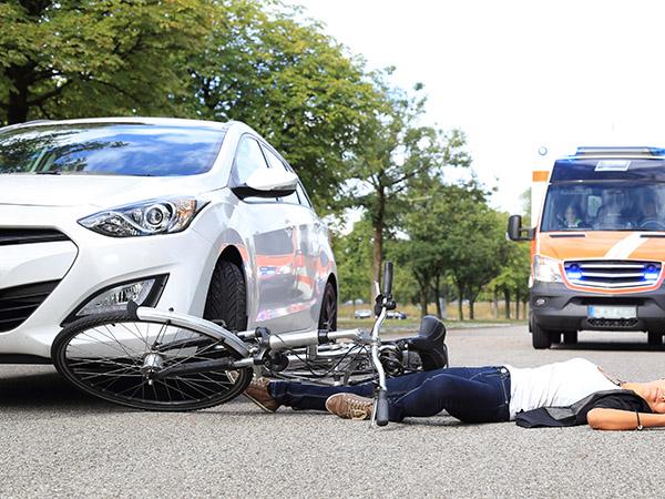交通事故直後道路に倒れる被害者と止まる車の写真