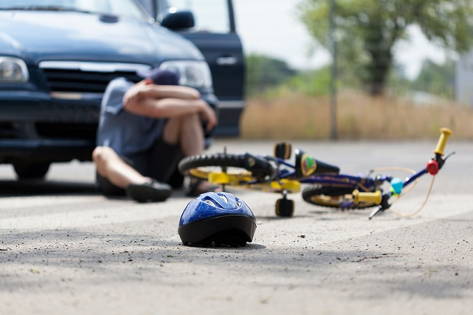 交通事故に遭って膝をかかえこむ子供のイメージ写真