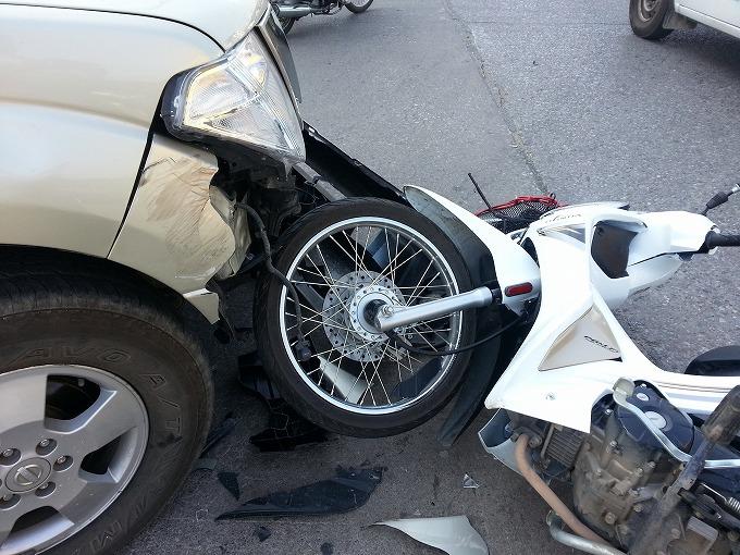 交通事故直後の車と原付バイクの写真