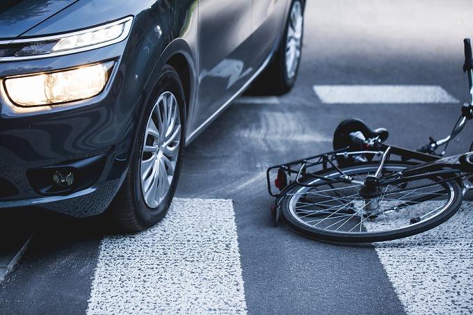 車とぶつかって横倒しになる自転車の写真
