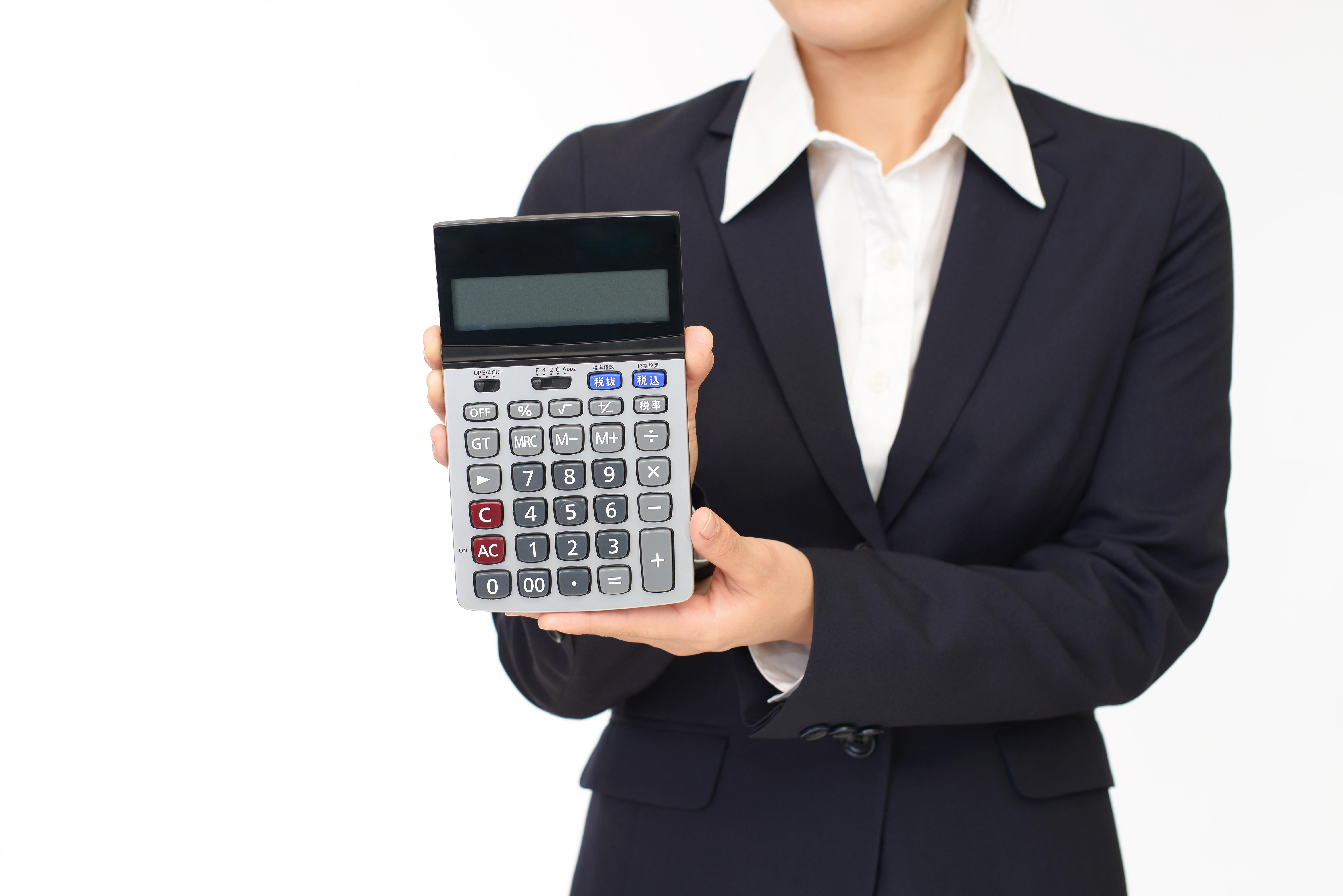 交通事故後の損害賠償もしくは慰謝料の金額を電卓で示す女性の写真