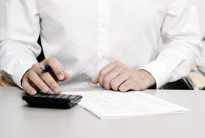 請求する慰謝料を電卓で計算する男性のイメージ画像
