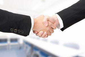 示談交渉で握手をしている2人の男性のイメージ画像