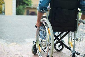 後遺障害のため車いすで移動する男性のイメージ画像