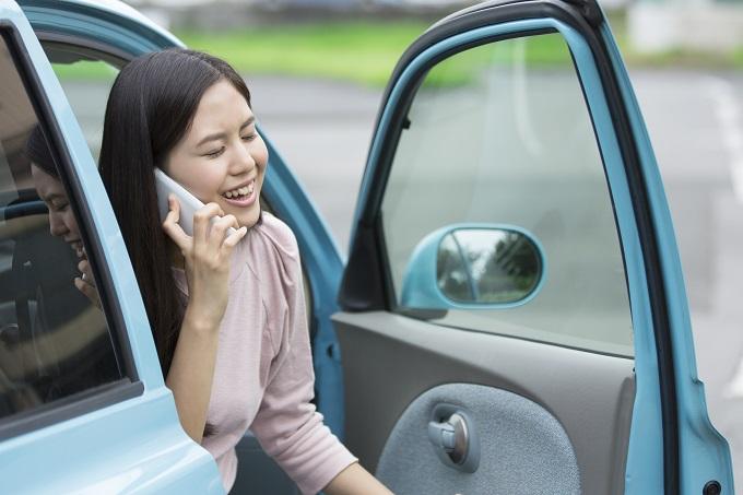 電話で話しながら車から出てくる女性のイメージ画像
