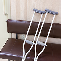病院の診察前の松葉づえと椅子のイメージ画像