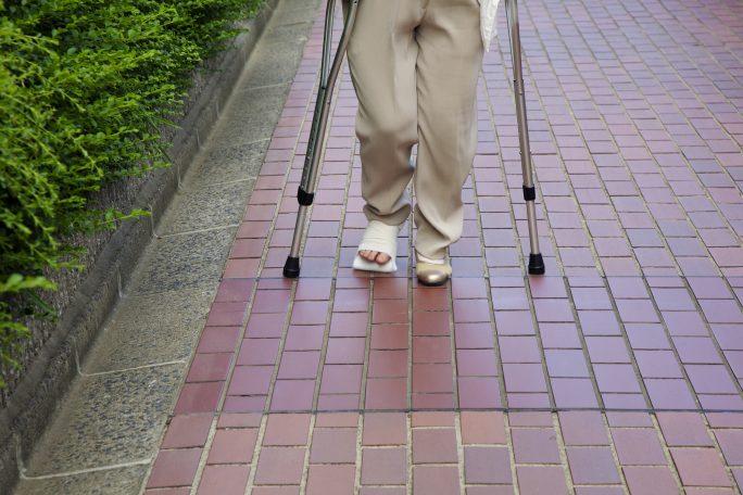 交通事故で骨折した足で通院する被害者のイメージ画像